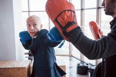 一个恼怒的秃头商人搅拌在健身房的拳击梨 愤怒管理的概念 库存图片