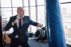 一个恼怒的秃头商人搅拌在健身房的拳击梨 愤怒管理的概念 免版税库存照片