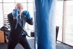 一个恼怒的秃头商人搅拌在健身房的拳击梨 愤怒管理的概念 免版税库存图片
