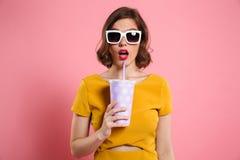 一个惊奇的女孩的画象拿着杯子的太阳镜的 免版税库存照片
