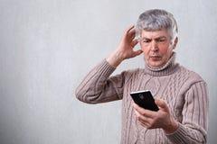 一个惊奇的年长人被冲击观看与他的智能手机的新闻 在他的智能手机的担心的老人读书正文消息 库存照片