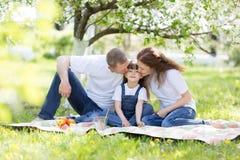 一个愉快的三口之家野餐的人 库存照片