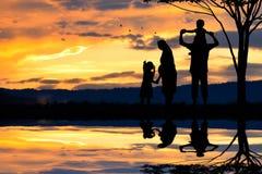 一个愉快的五口之家的剪影人、母亲、父亲、婴孩、孩子和婴儿(妇女prenancy) 免版税库存图片