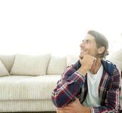 一个愉快的人的特写镜头坐在一栋新的公寓的地毯 图库摄影