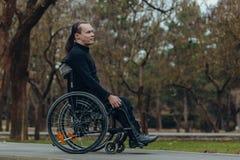 一个愉快的人的画象一个轮椅的在公园 免版税库存照片
