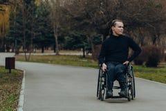 一个愉快的人的画象一个轮椅的在公园 库存照片