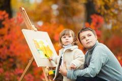 一个愉快的兄弟和姐妹在秋天公园绘 本质上,露天走 免版税库存图片