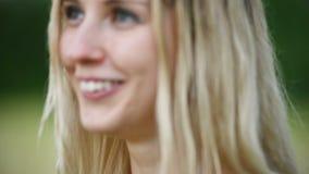 一个愉快的可爱的白种人白肤金发的女孩的特写镜头画象有湿头发的在自然的雨期间室外在a 影视素材