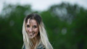 一个愉快的可爱的白种人白肤金发的女孩的特写镜头画象有湿头发的在自然的雨期间室外在a 股票视频