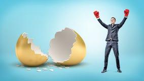 一个愉快的商人举他的在胜利佩带的拳击手套的手并且在一个残破的金黄鸡蛋附近站立 免版税库存图片