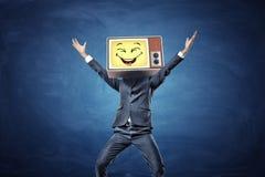 一个愉快的商人用在胜利举的手有与一张黄色兴高采烈的面孔的减速火箭的电视而不是他的头 免版税图库摄影