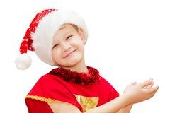 一个愉快的圣诞节孩子的画象在whi隔绝的圣诞老人帽子的 免版税库存照片
