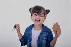 一个愉快的女孩去搬到一个新房并且把握关键对一栋新的公寓 免版税库存照片