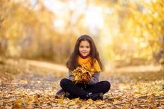 一个愉快的女孩在秋天森林里走 库存照片