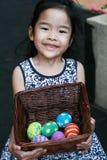 一个愉快的女孩用五颜六色的复活节彩蛋 免版税库存图片