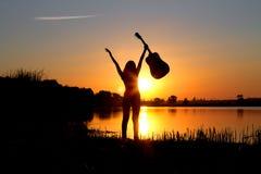 一个愉快的女孩的剪影有一把吉他的在自然 免版税库存照片