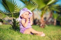 一个愉快的女孩的画象在度假 紫色的一个女孩坐草坪 库存图片
