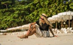 一个愉快的女孩的纵向 早晨坐沙滩,佩带的太阳镜 空白伞背景 纹身花刺 库存图片