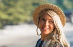 一个愉快的女孩的纵向 早晨坐沙滩,微笑对照相机 特写镜头 免版税库存图片