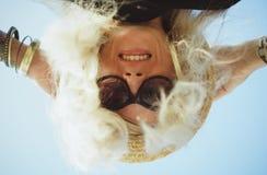 一个愉快的女孩的纵向 早晨坐沙滩,微笑对照相机 特写镜头 图库摄影