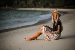 一个愉快的女孩的纵向 早晨坐沙滩,微笑对照相机 免版税库存图片
