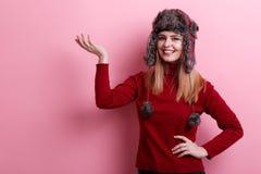 一个愉快的女孩,微笑和握一只手的一个温暖的帽子和甜点的在顶头水平 桃红色背景 免版税库存照片