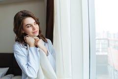 一个愉快的妇女开窗口帷幕的画象 图库摄影