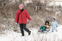 一个愉快的孩子以冬天时尚在他的村庄房子庭院给摆在与玩具猪穿衣 第一雪,家庭,传统 图库摄影