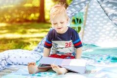 一个愉快的孩子在公园读一本书 男孩幼儿园 夏天 T 免版税库存照片