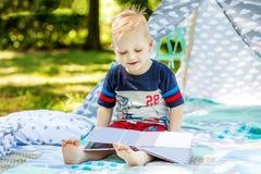 一个愉快的孩子在公园读一本书 男孩幼儿园 conce 免版税库存图片