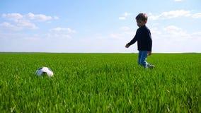 一个愉快的孩子通过绿草的领域在慢动作的走并且踢足球 股票视频