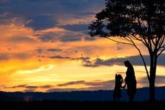 一个愉快的家庭、母亲、女孩和婴儿(妇女怀孕)的剪影有树的在被弄脏的日落天空在山 免版税库存照片