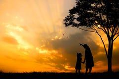 一个愉快的家庭、母亲、女孩和婴儿(妇女怀孕)的剪影有树的在被弄脏的日落天空在山 库存图片