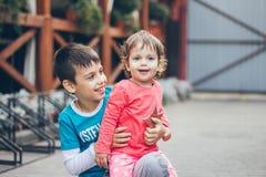 一个愉快的家庭儿童兄弟姐妹男孩和女孩一起使用并且微笑,姐妹和兄弟 库存图片