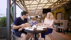 一个愉快的家庭和他们的儿子的图象咖啡馆的 爱恋的加上孩子在比萨店一起花费时间 影视素材