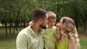 一个愉快的家庭的画象与一个小儿子的在公园在夏天 慢的行动 影视素材