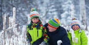 一个愉快的家庭的画象在冬天公园 父亲,儿子和一点女儿笑 库存图片