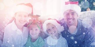 一个愉快的家庭的画象的综合图象与圣诞节帽子的坐沙发 免版税库存图片