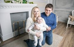 一个愉快的家庭的画象:母亲、父亲和岁孩子在客厅 图库摄影