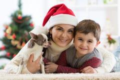 一个愉快的家庭的画象和在家一起花费圣诞节时间的狗在x-mas树附近 图库摄影