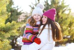 一个愉快的家庭的画象,有孩子的母亲获得乐趣在冬天 免版税库存图片