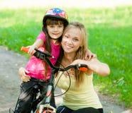 一个愉快的家庭的画象,骑一辆自行车在公园 免版税图库摄影