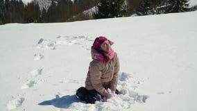 一个愉快的小女孩投掷雪 她笑 女孩在冬天森林里走本质上在山的 股票视频