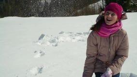 一个愉快的小女孩投掷雪 她笑 女孩在冬天森林里走本质上在山的 影视素材