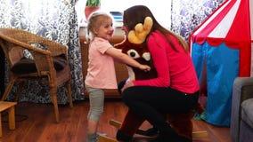 一个愉快的小女孩摇摆她的一头玩具鹿的母亲在慢动作 股票录像