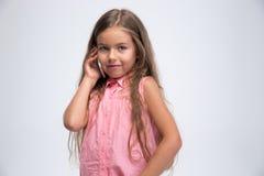 一个愉快的小女孩的画象谈话在电话 库存图片