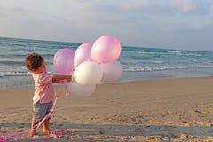 一个愉快的小男孩使用与在海滩的气球 免版税图库摄影