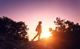 一个愉快的少妇的剪影山的在日落 免版税库存图片