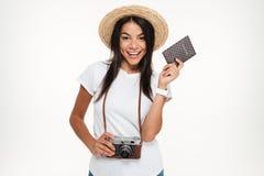 一个愉快的少妇的画象拿着照相机的帽子的 免版税图库摄影