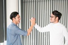 一个愉快的年轻人的画象在拍他们的手的办公室好打手势亚裔聪明的英俊的人民 库存照片